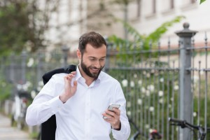 Smiling Handsome Man Using Phone While Walking