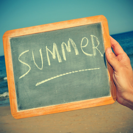 picture of someone on the beach holding a blackboard with the word summer written on it, with a retro effect